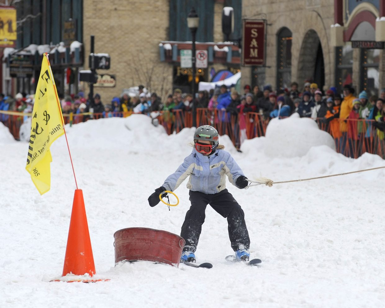 Nine-year-old Jade Henderson tries to get a ring into a bucket during the Winter Carnival street events Saturday.