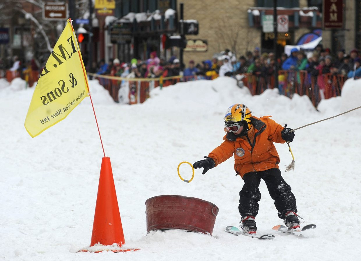 Oliver Van De Carr drops a ring in the bucket during the Winter Carnival street events Saturday.