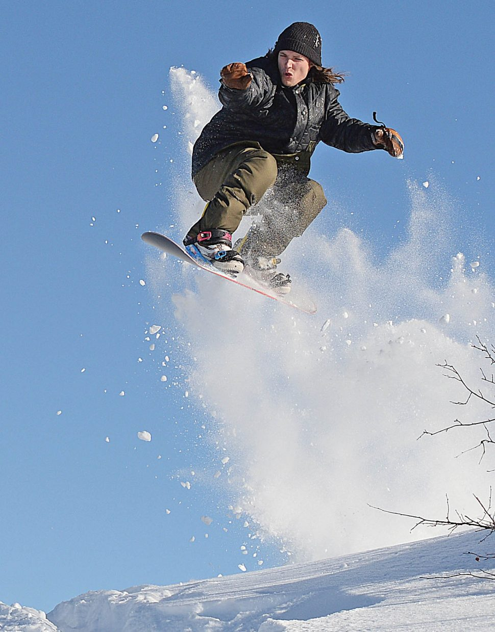Colorado Mountain College student Jared Bennett hits a jump at the base of Howelsen Hill Tuesday while taking advantage of a great, blue-sky day to snowboard with friends.