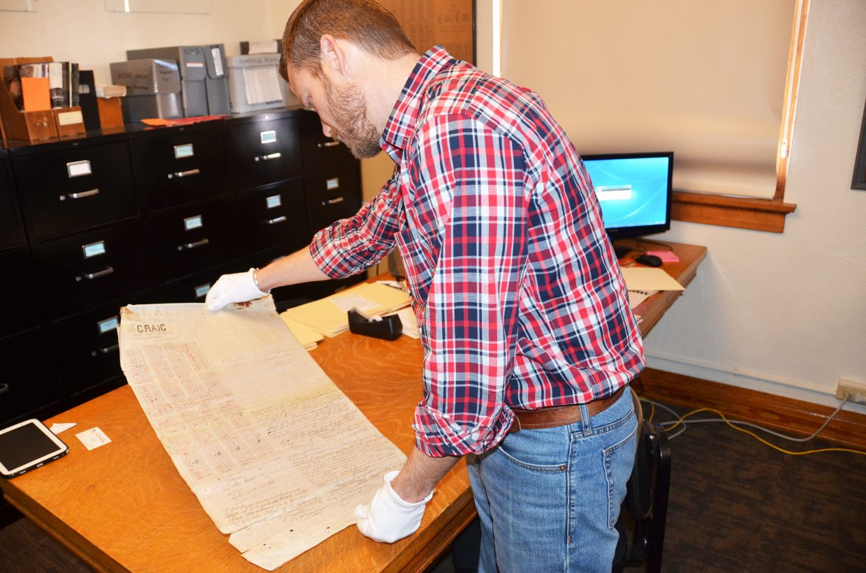 Paul Knowles, assistant director of the Museum of Northwest Colorado, examines a plat map of Craig, dated 1889.