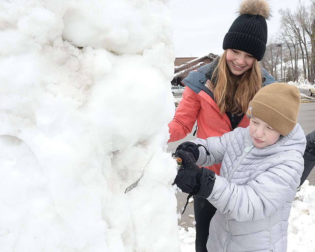 Steamboat Springs High School students Ashley Herzog, front, and Autumn Graham work on a snow sculpture at the corner of Third Street and Lincoln Avenue Thursday morning.