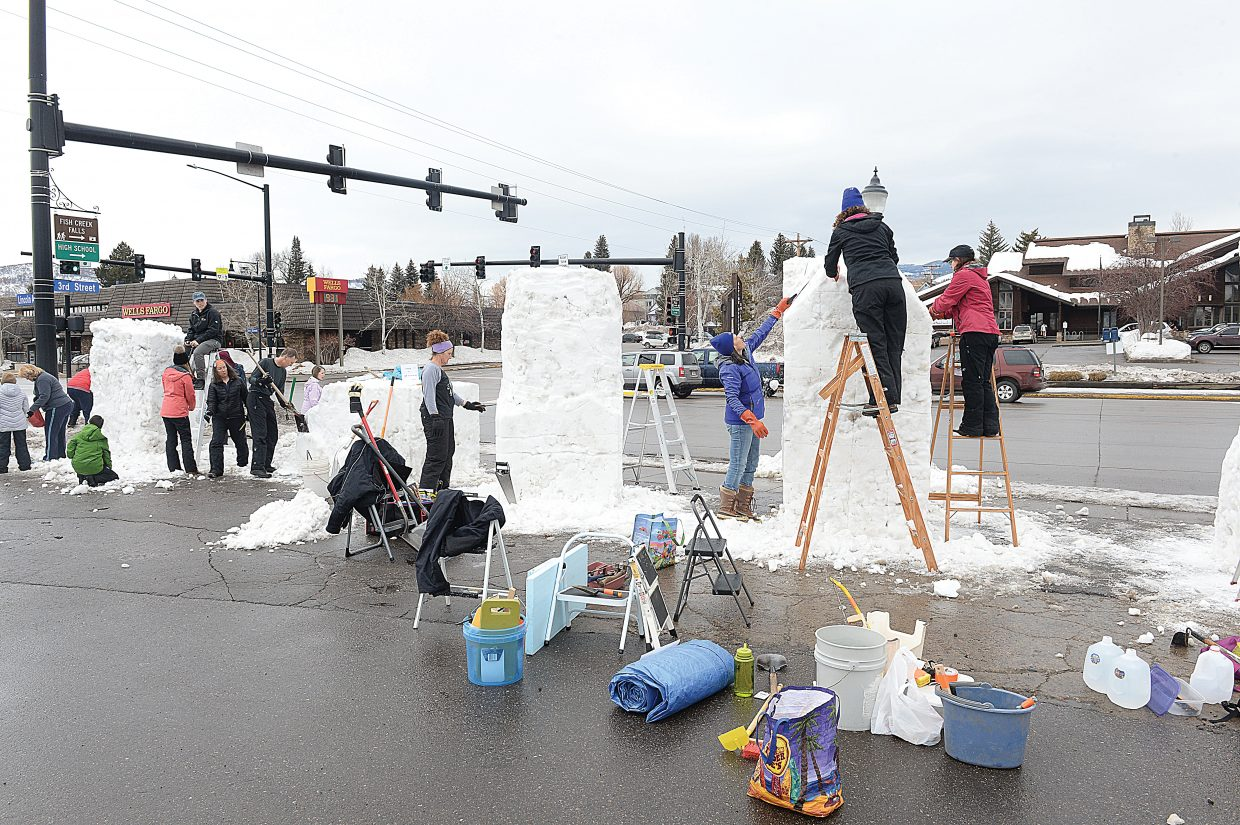 Teams made up of students and community members work together to create snow sculptures at the corner of Third Street and Lincoln Avenue.