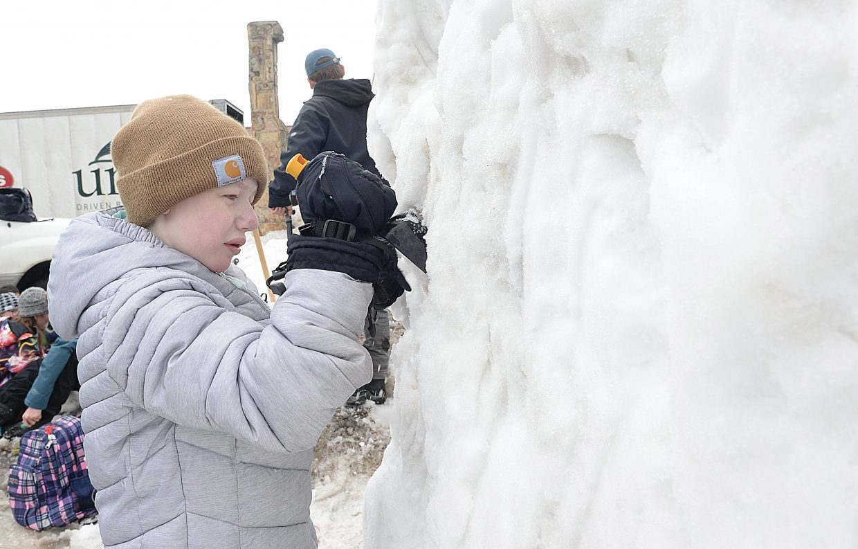 Steamboat Springs High School student Ashley Herzog works on a snow sculpture at the corner of Third Street and Lincoln Avenue Thursday morning.