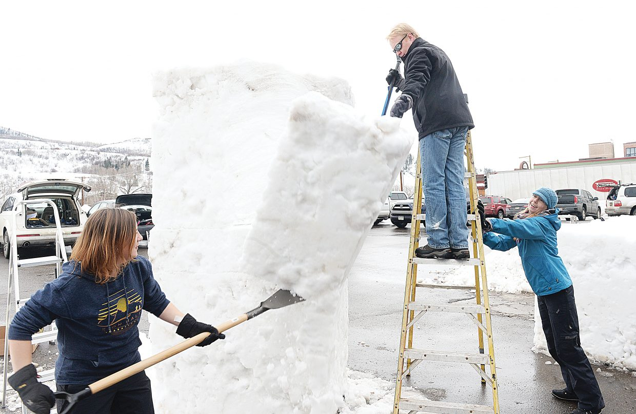 Karyn Savory and Greg Effinger (on ladder) break off a huge chunk of snow while working on a snow sculpture as part of this year's Winter Carnival celebration. Jessica Marion was there to steady the ladder.