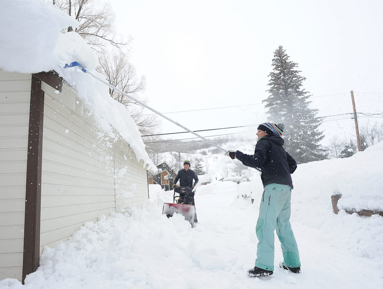 Kate Rench uses a snow rake to remove snow from the roof of her garage while Craig Rench uses a snow blower. Heavy snow during the weekend has left several feet of snow on roofs in the Steamboat area.