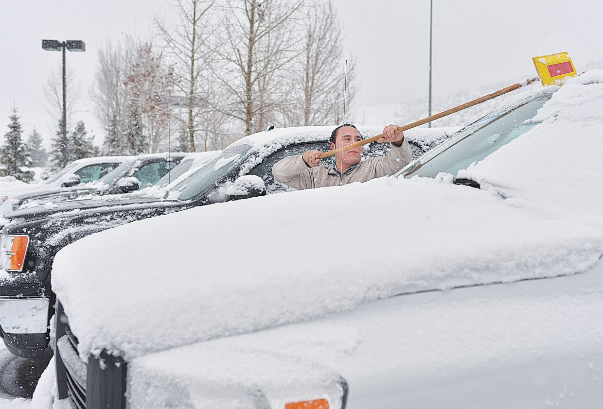 Cook Chevrolet and Subaru employee Jorge Sanchez clears off snow from the cars at the Steamboat Springs lot. After a warmer than average day Monday, the cool temperatures and snow returned to Steamboat Tuesday morning. Sunny skies and warmer temperatures by the afternoon melted off any accumulation.