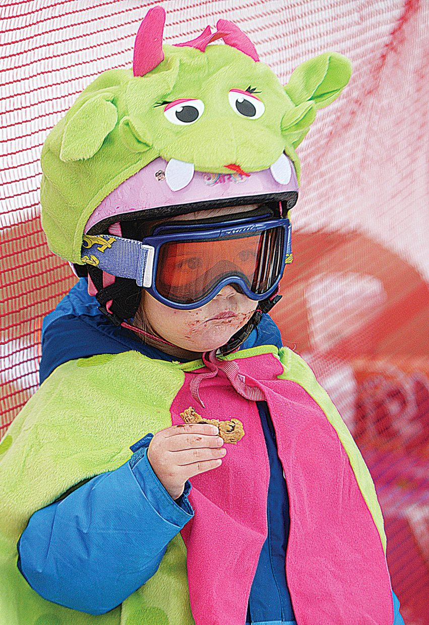 Mary Novotny eats a cookie near the finish of this year's Soda Pop Slalom at Steamboat Ski Area Friday morning. The 2-year-old wasn't old enough to race but was there to support her older sister Klara, who was a Winter Carnival princess this year. Mary decided to dress up like a dragon after her parents read a story to her about how it's a dragon's job to protect princesses.