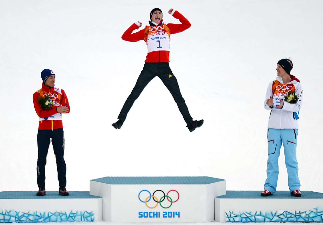 Eric Frenzel leaps on to the podium Wednesday after winning gold in the men's normal hill Nordic combined competition at the 2014 Winter Olympics.