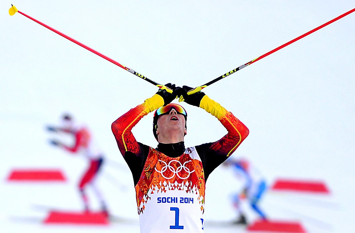 German Eric Frenzel raises his arms above his head as he crosses the finish line Wednesday during the men's normal hill Nordic combined competition in Krasnaya Polyana, Russia. Frenzel won the gold medal in the event.