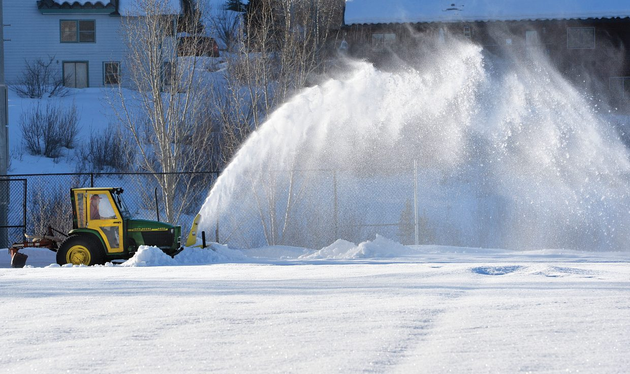 """Greg LaPointe, a Steamboat Springs School District employee, used a snowblower to remove snow from the Steamboat Springs High School track Wednesday moring. LaPointe said a """"snowcat"""" will be used later this week to push snow off the artificial surface."""