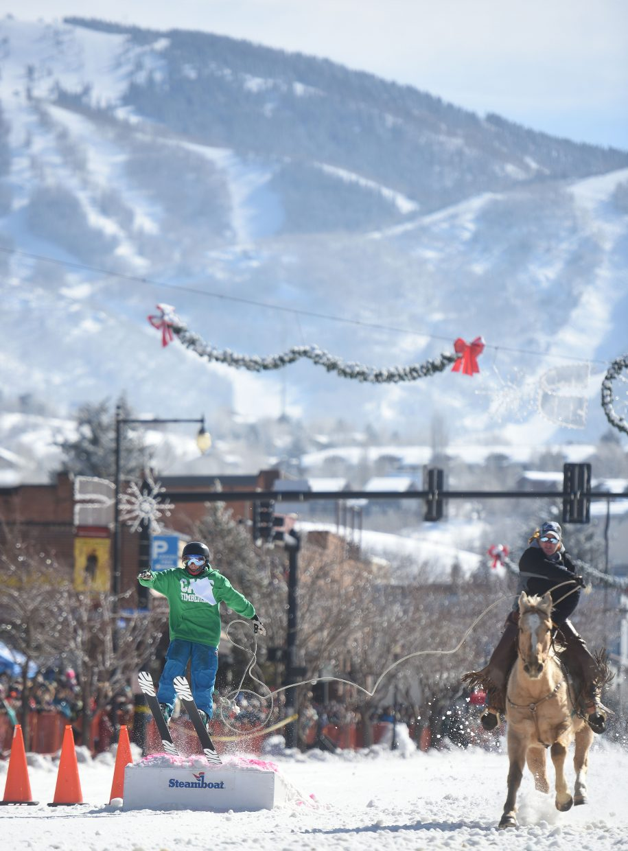 Skier, horse and rider charge down the street Sunday during Winter Carnival in Steamboat Springs.