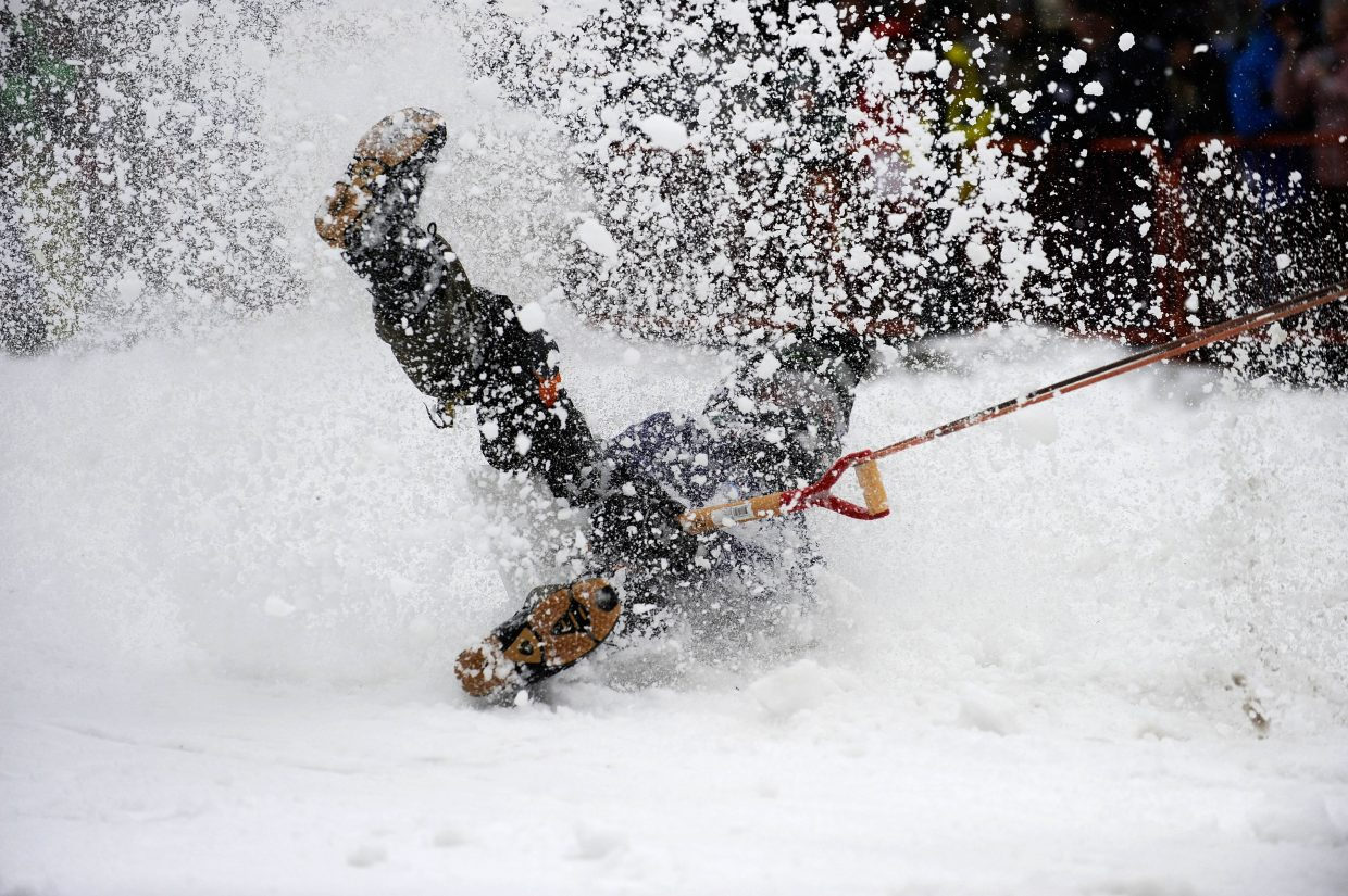 JJ Egloff gets dragged by a horse in the Shovel Race competition Saturday during the Steamboat Springs Winter Carnival Street Events.
