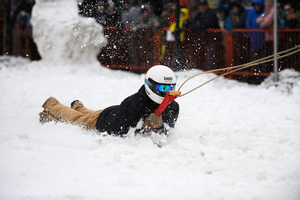 Andy Picking holds on in the Shovel Race competition Saturday during the Steamboat Springs Winter Carnival Street Events.