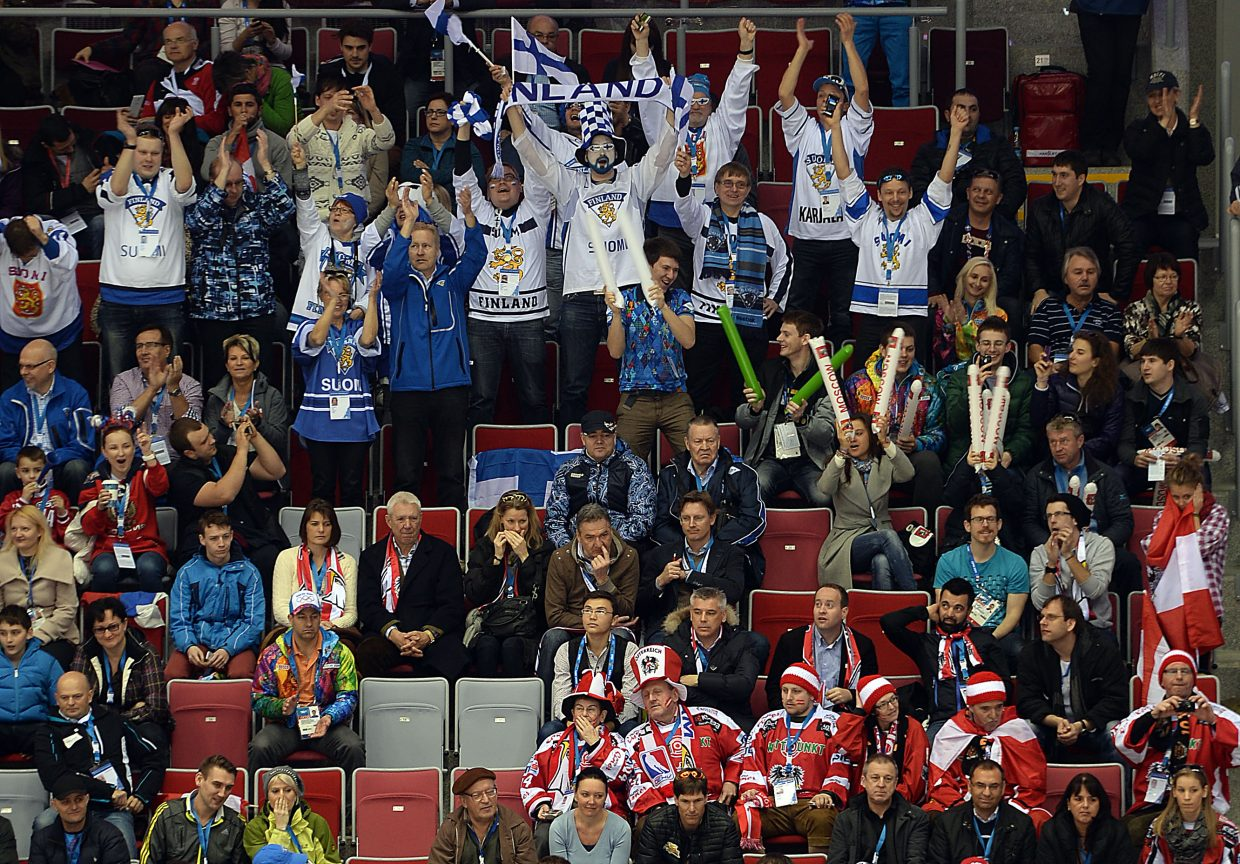 Finnish hockey fans react to a goal while the nearby Austrians sulk.