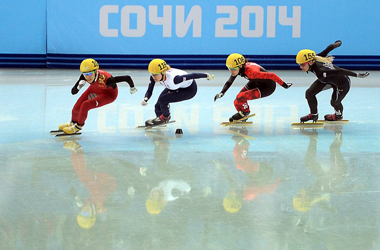 China's Kexin Fan, Great Britian's Elise Christie, Canada's Jessica Hewitt and the United States' Emily Scott cut around the track during the women's 500-meter short track speed skating quarterfinals on Thursday at the 2014 Winter Olympics in Russia.