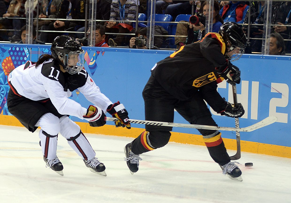 Japan's Yurie Adachi reaches to poke away the puck Thursday against Germany.