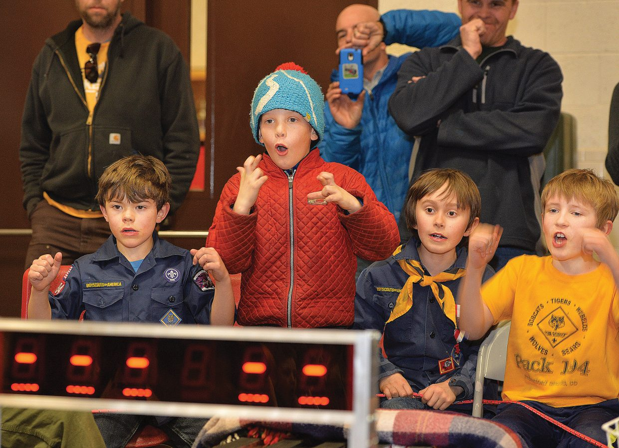 Trout Alford, in the red coat, cheers as his car approaches the finish line at the Cub Scout's Pinewood Derby event Wednesday evening at the Steamboat Springs Middle School.