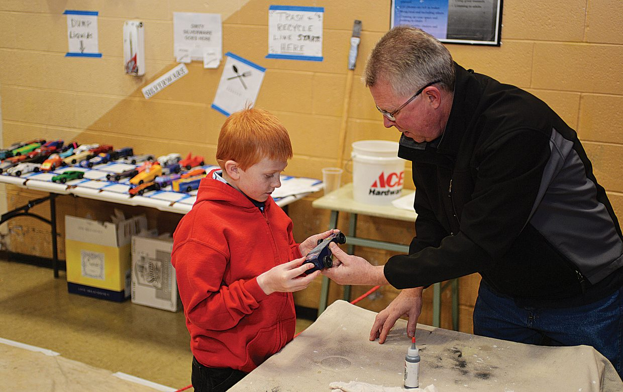 Dave Laughlin hands his son Nolan his Pinewood racer Wednesday before the start of the Cub Scout's annual Pinewood Derby at the Steamboat Springs Middle School.