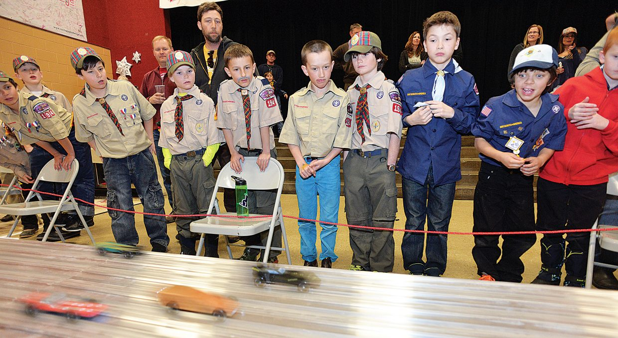 Cub Scouts watch as the first heat of Pinewood racers make their way down the track. The Boy Scouts hosted the annual Pinewood Derby Wednesday evening at the Steamboat Springs Middle School.
