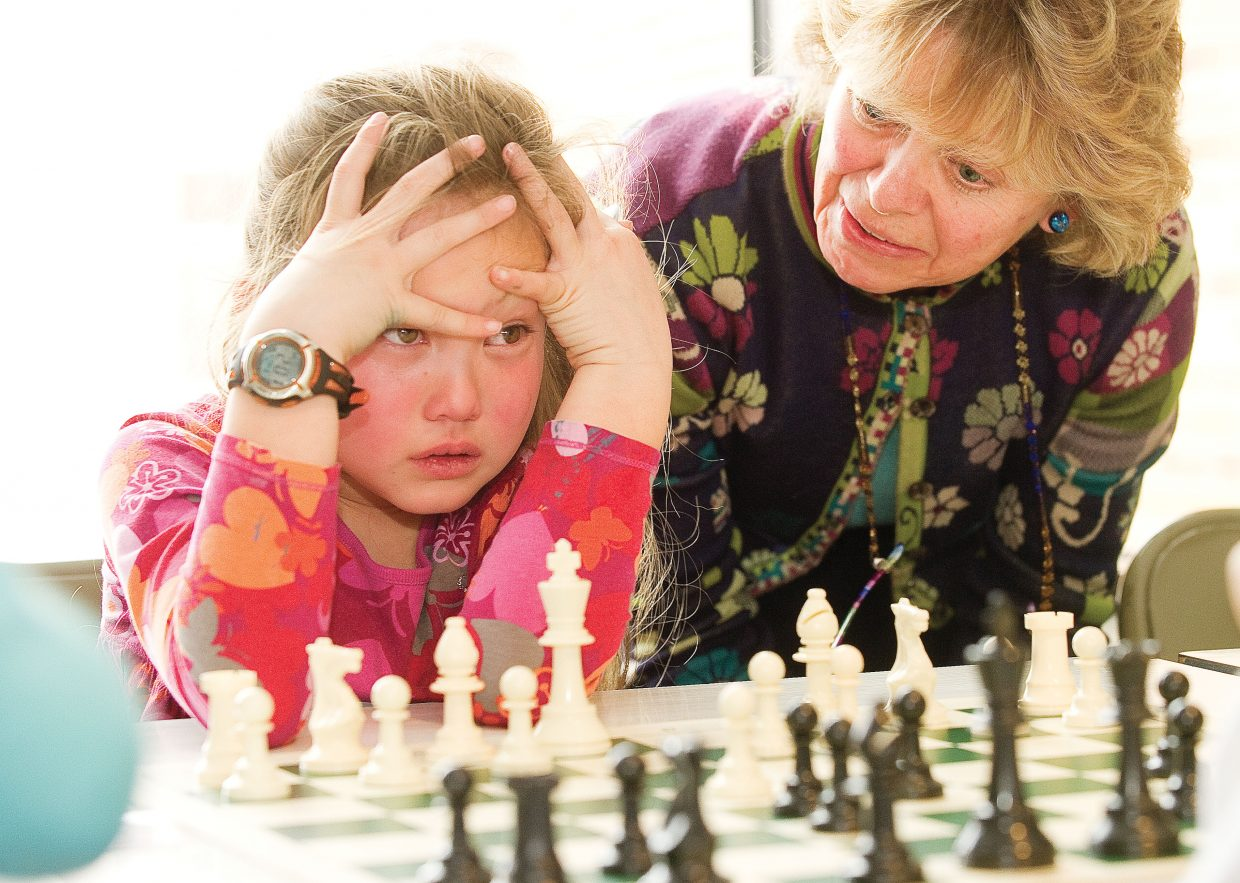 Volunteer Claire Sollars offers Carolee Taylor-Hall some advice during a chess match at Strawberry Park Elementary School. More than 50 students took part in a chess tournament at the school.