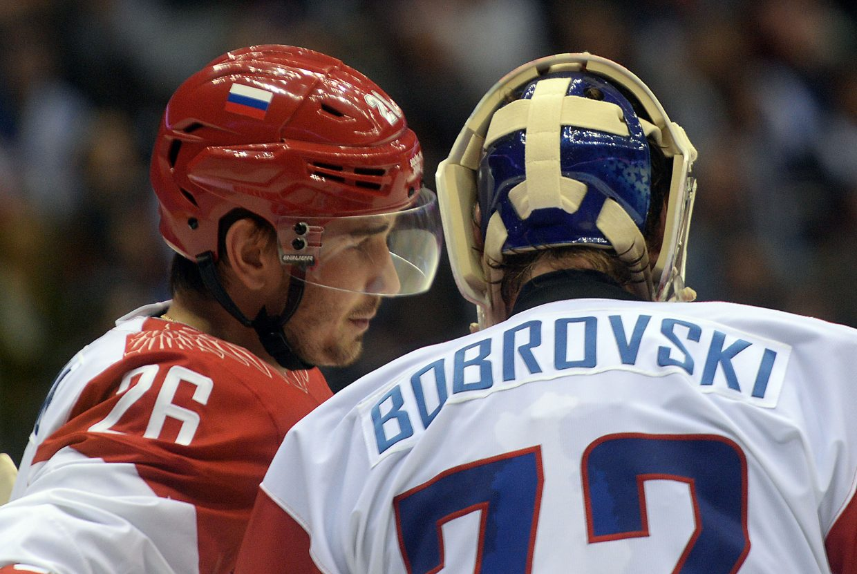 Alexander Popov talks with Russian goalie Sergei Bobrovski on Saturday during the Russia mens hockey team's game against the United States.