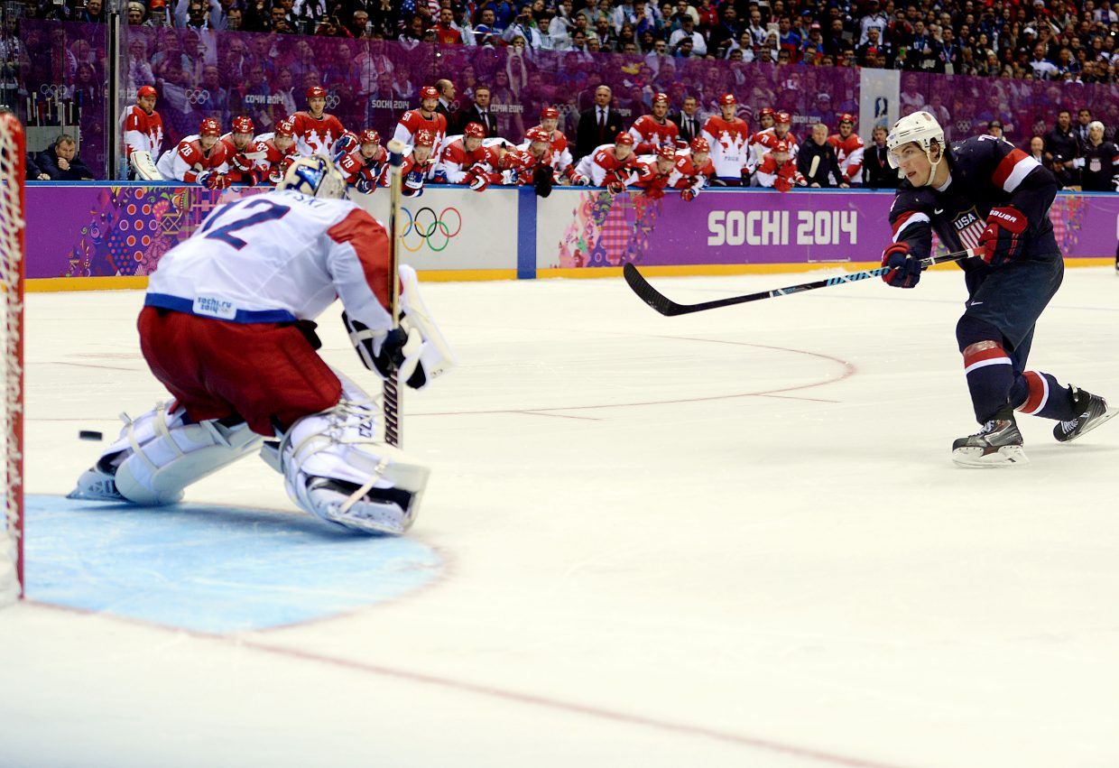 TJ Oshie slides a puck past Russian goalkeeper Sergei Bobrovsky on Saturday night in at the Bolshoy Ice Dome in Sochi, Russia. The shootout goal gave the United States a dramatic win against the host Russians during pool play of the men's ice hockey tournament.