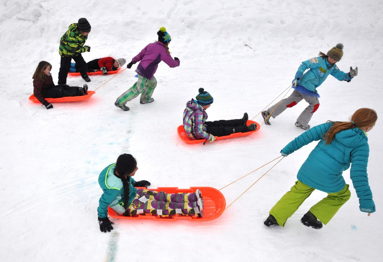 Strawberry Park Elementary School students compete Friday in a sledding event during the Olympic Winter SnowFest. The event also featured hockey, curling, snowshoe racing and other activities.