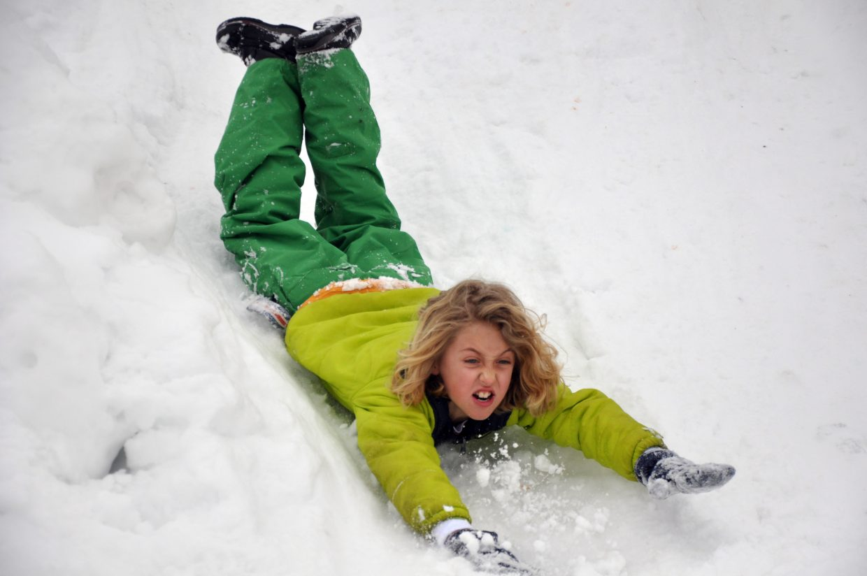 Giovanni Demusis slides headfirst down a sledding hill at Strawberry Park Elementary School during the Olympic SnowFest.