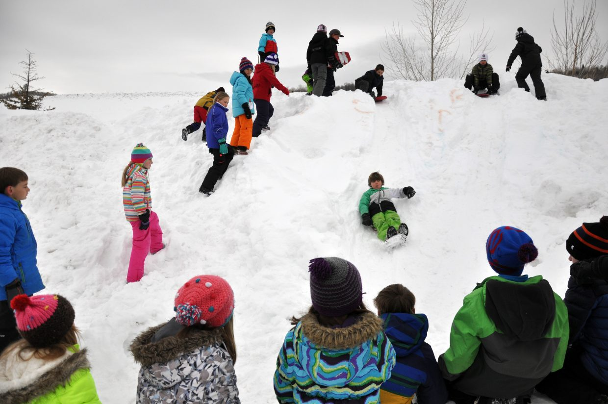 Strawberry Park Elementary School students watch their classmates go down a sledding hill Friday during the Winter Olympic SnowFest.