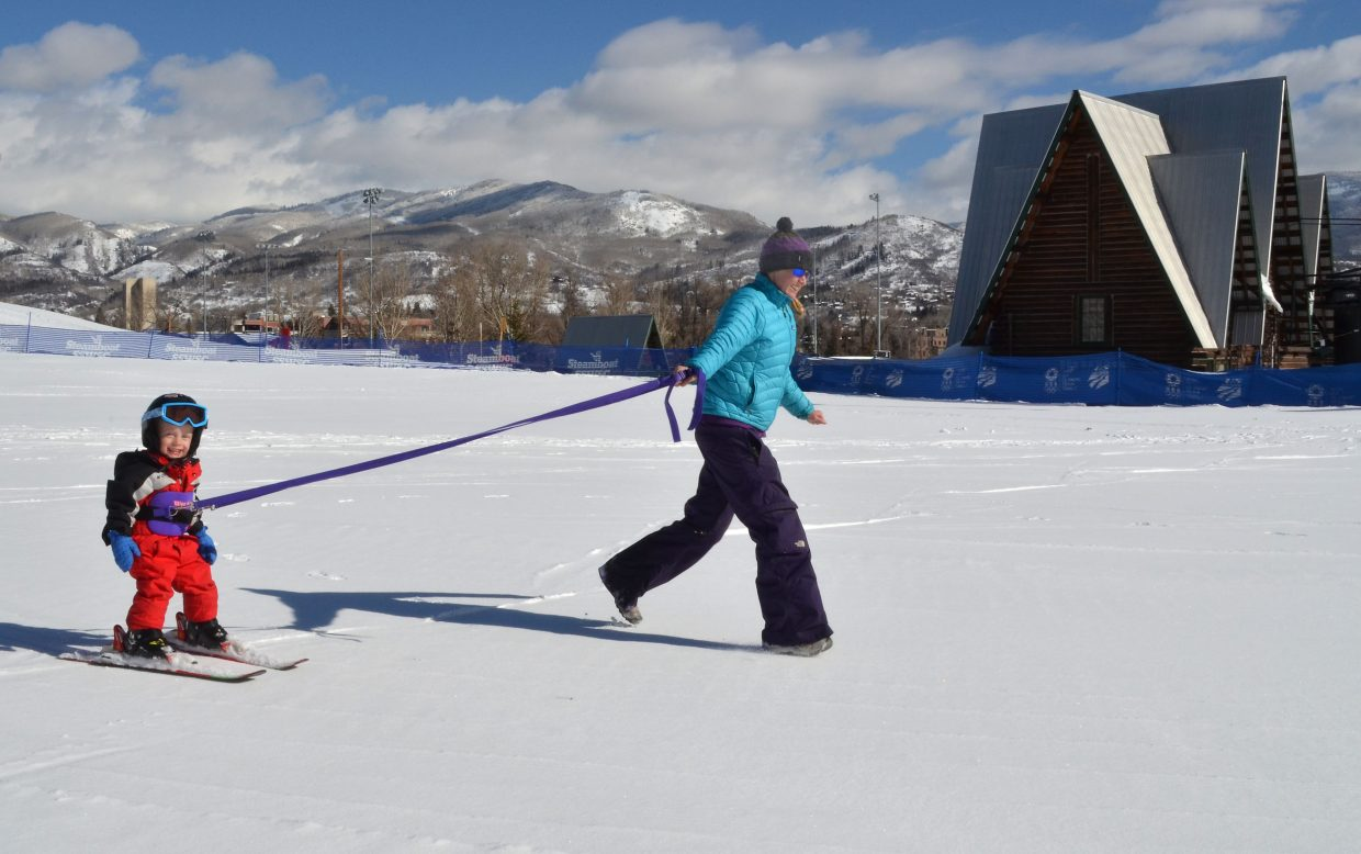 Sam Pulford, 2, gets a cheap thrill while playing crack the whip on skis with his mother Tiffani at Howelsen Hill with the historic tow house in the background.