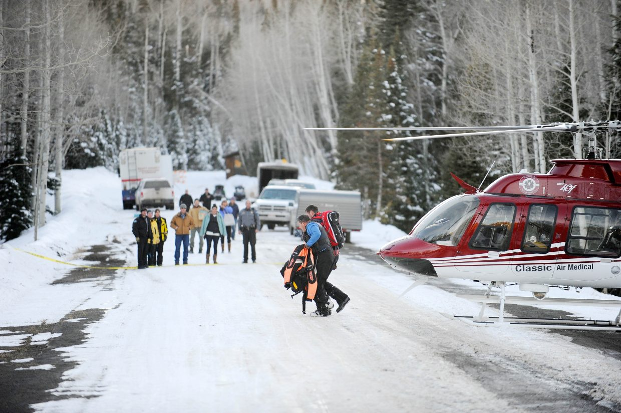 Avalanche survivor Sean Searle gets help walking away from a helicopter Tuesday after being rescued in the Flat Tops Wilderness.