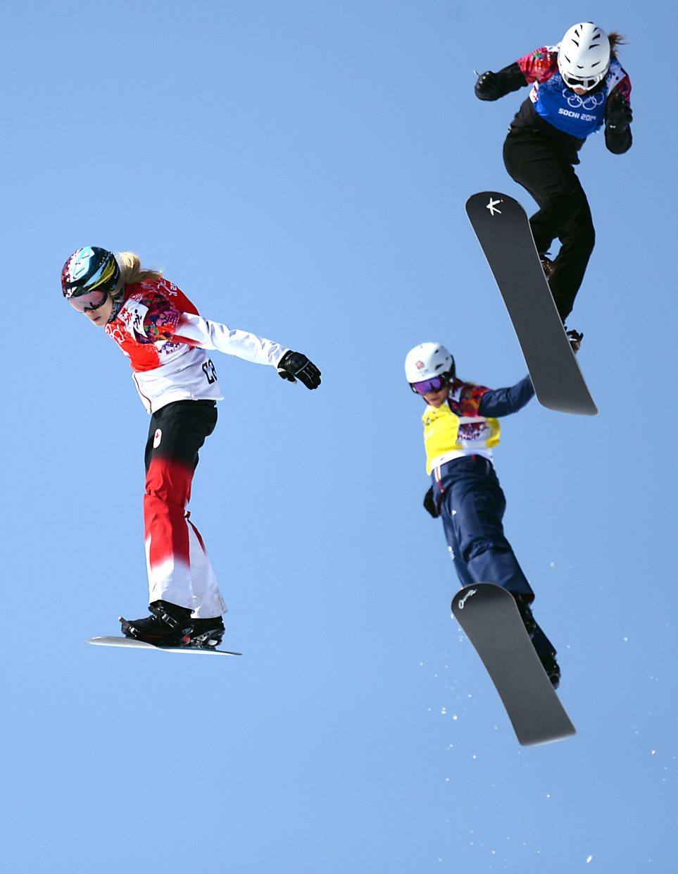 Dominique Maltais leads her quarterfinals heat over the jump in front of the finish line Sunday at the women's snowboard cross event.