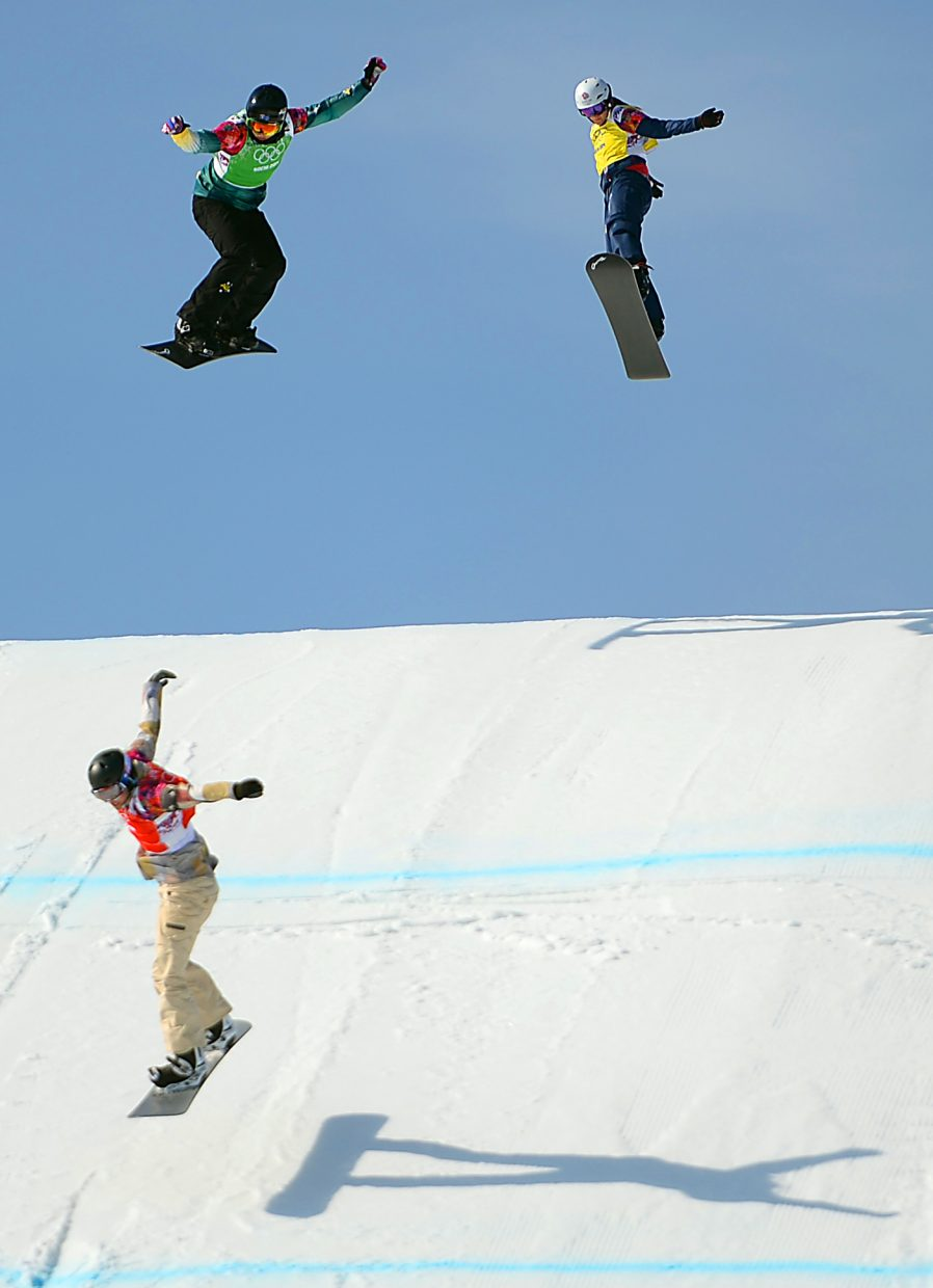 Lindsey Jacobellis leads the way, landing ahead of Australian and former Steamboat Springs snowboarder Belle Brockhoff, left, and Great Britian's Zoe Gillings, right. Jacobellis won the race, the small final, placing her seventh and Brockoff eighth in the overall standings for women's snowboard cross at the 2014 Winter Olympics.
