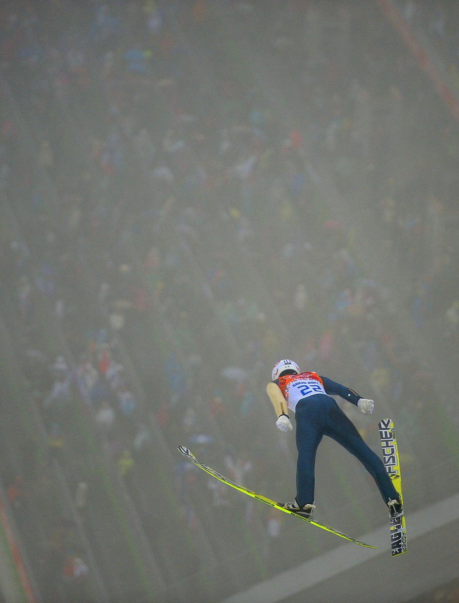 Nordic combined competitor Taihei Kato flies through the fog Tuesday during the large hill Nordic combined competition at the 2014 Winter Olympics.