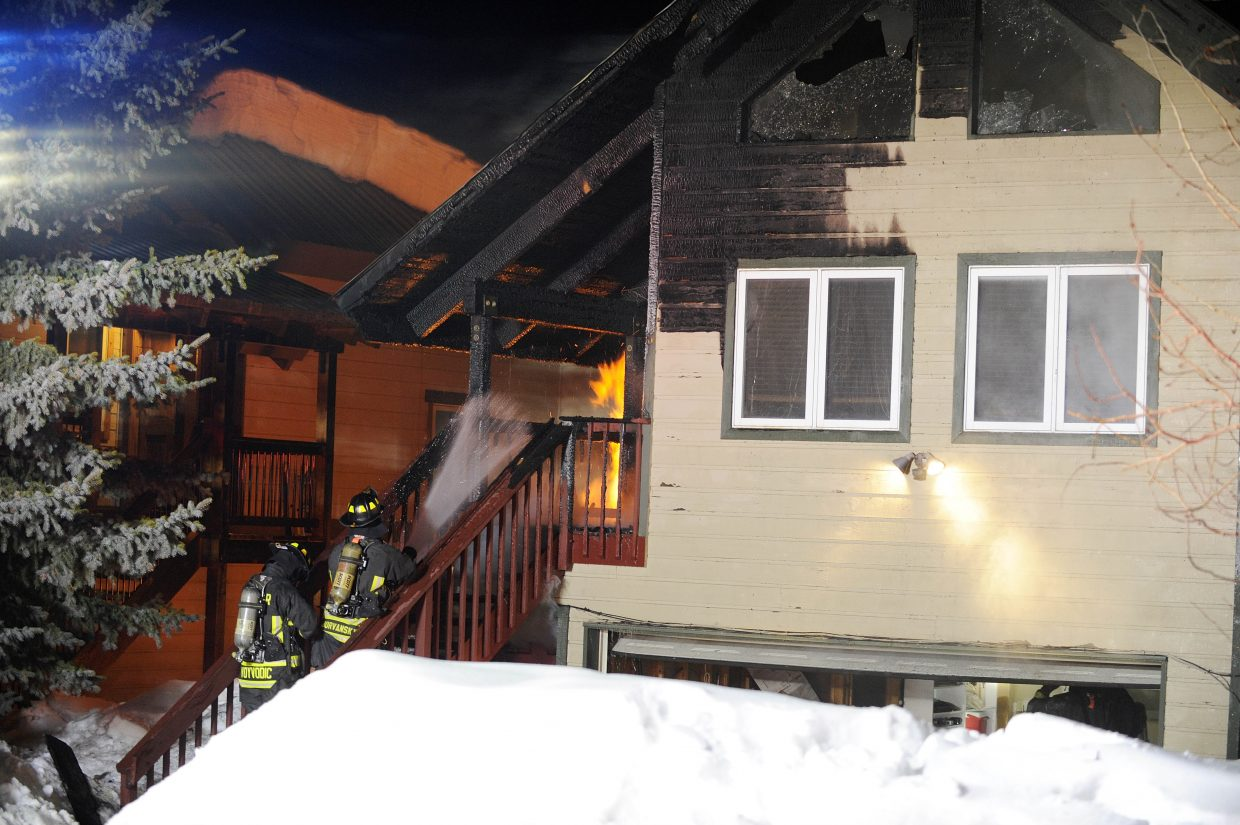 Steamboat Springs Fire Rescue firefighters work to put out flames Tuesday night at a duplex at 366 Cherry Drive. No injuries were reported.