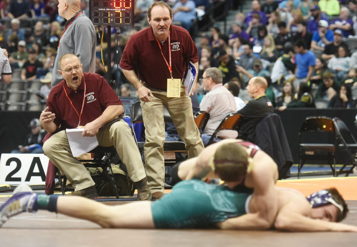 Soroco coaches Travis Bruggink, left, and Jay Whaley cheer on senior Lane Martindale on Thursday at the state wrestling tournament in Denver.