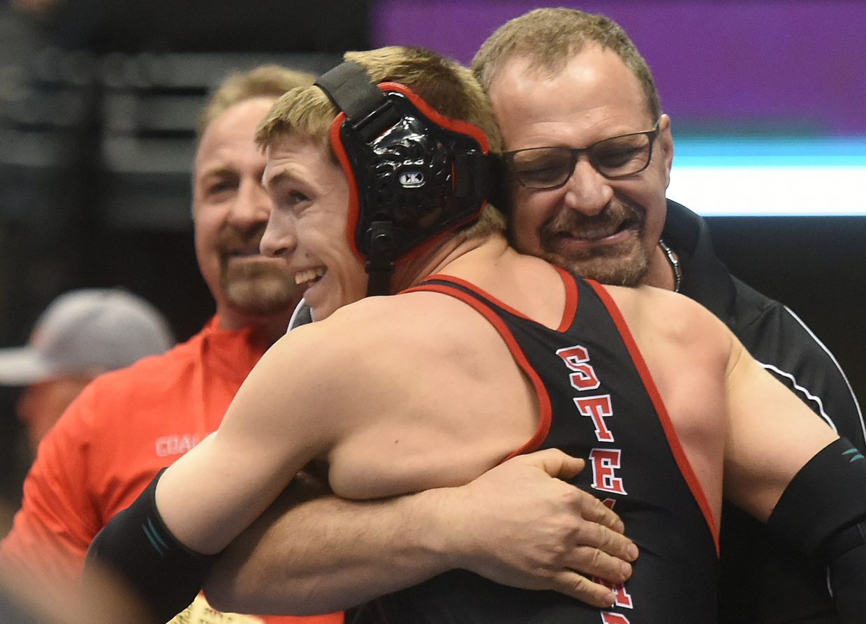 Steamboat coach Travis Bryant hugs his son, Lance Bryant, after a quarterfinals win at the state wrestling tournament.