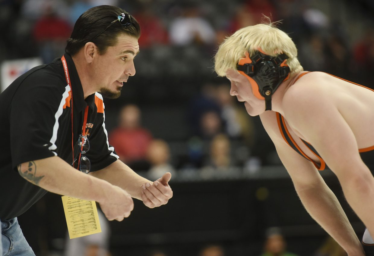 Hayden coach Chad Jones leans in to talk with senior Christian Carson on Friday at the state wrestling tournament in Denver.
