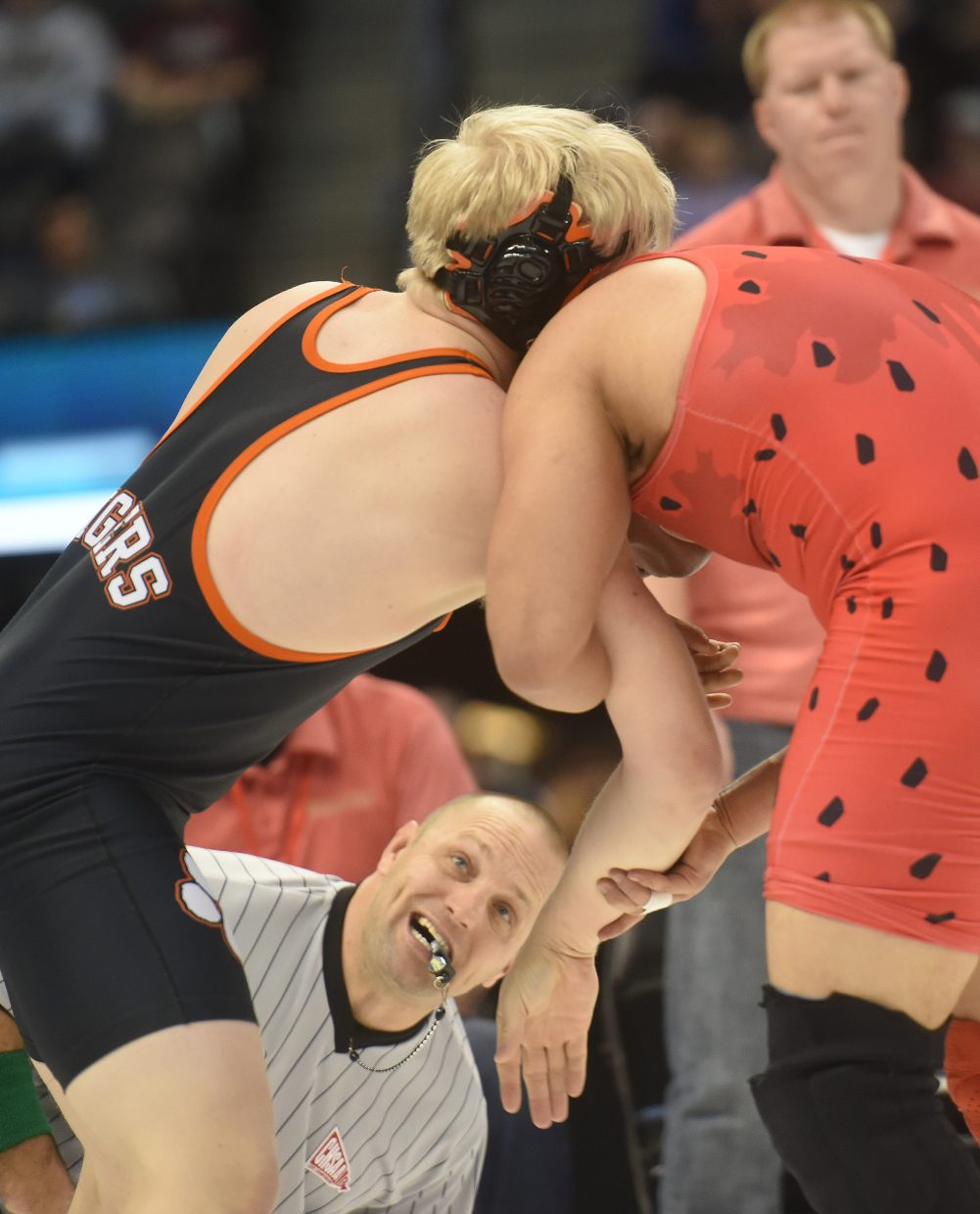 An official looks in as Hayden's Christian Carson wrestles against Ricky Preciado of Rocky Ford on Friday at the state wrestling tournament in Denver.