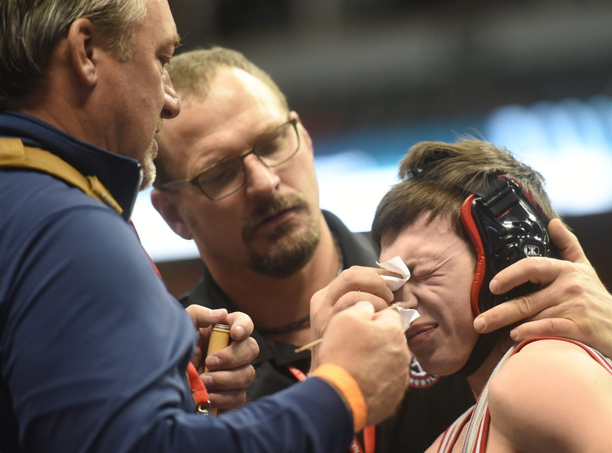Steamboat senior Colton Pasternak winces while a bloody spot on his nose is attended to Friday at the state wrestling championships in Denver.