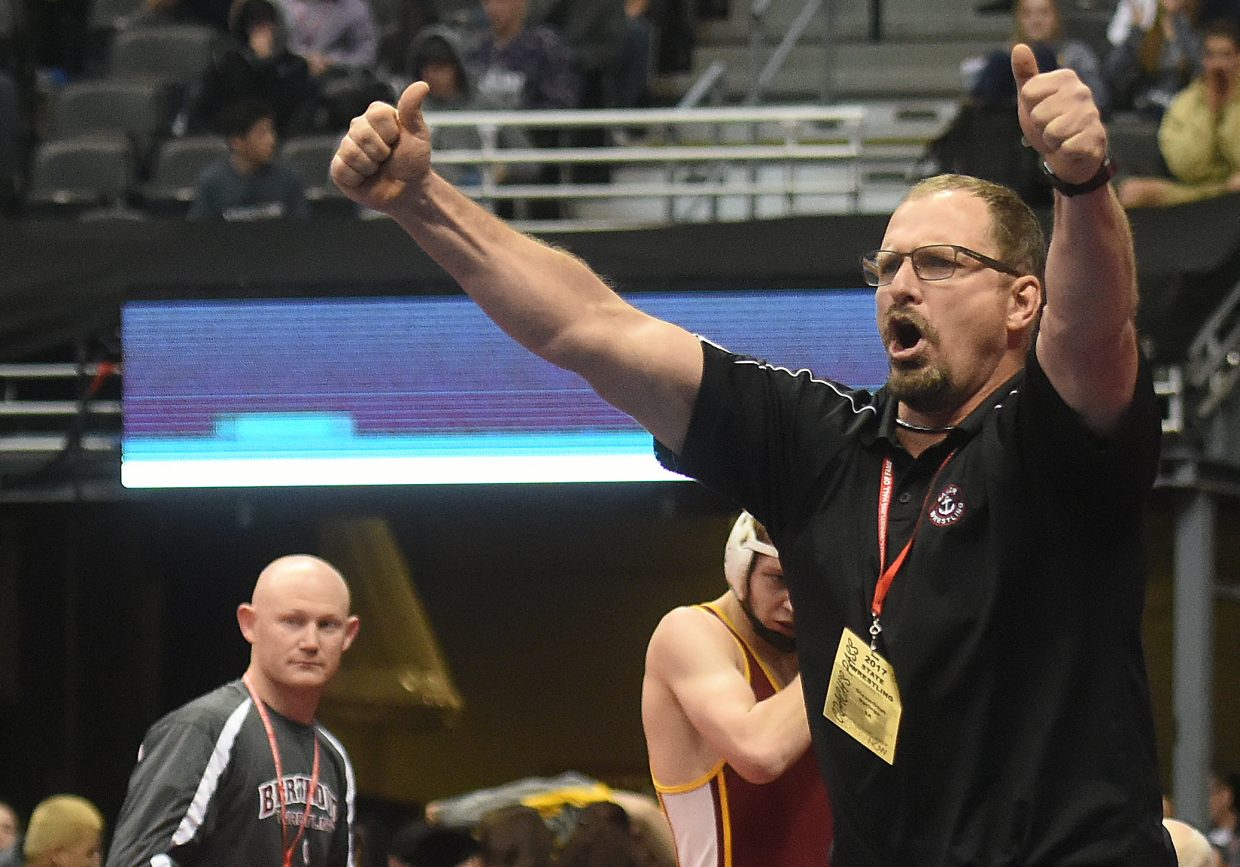 Steamboat coach Travis Bryant celebrates as his son, 145-pound junior Lance Bryant, finishes off a win at the state wrestling tournament.