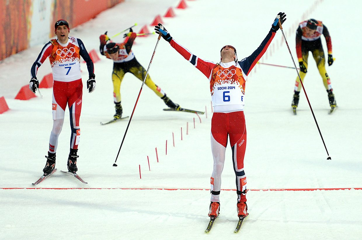 Norway's Joergen Graabak throws his arms up and looks to the heavens as he crosses the finish line of Tuesday's Nordic combined large hill event at the 2014 Winter Olympics.