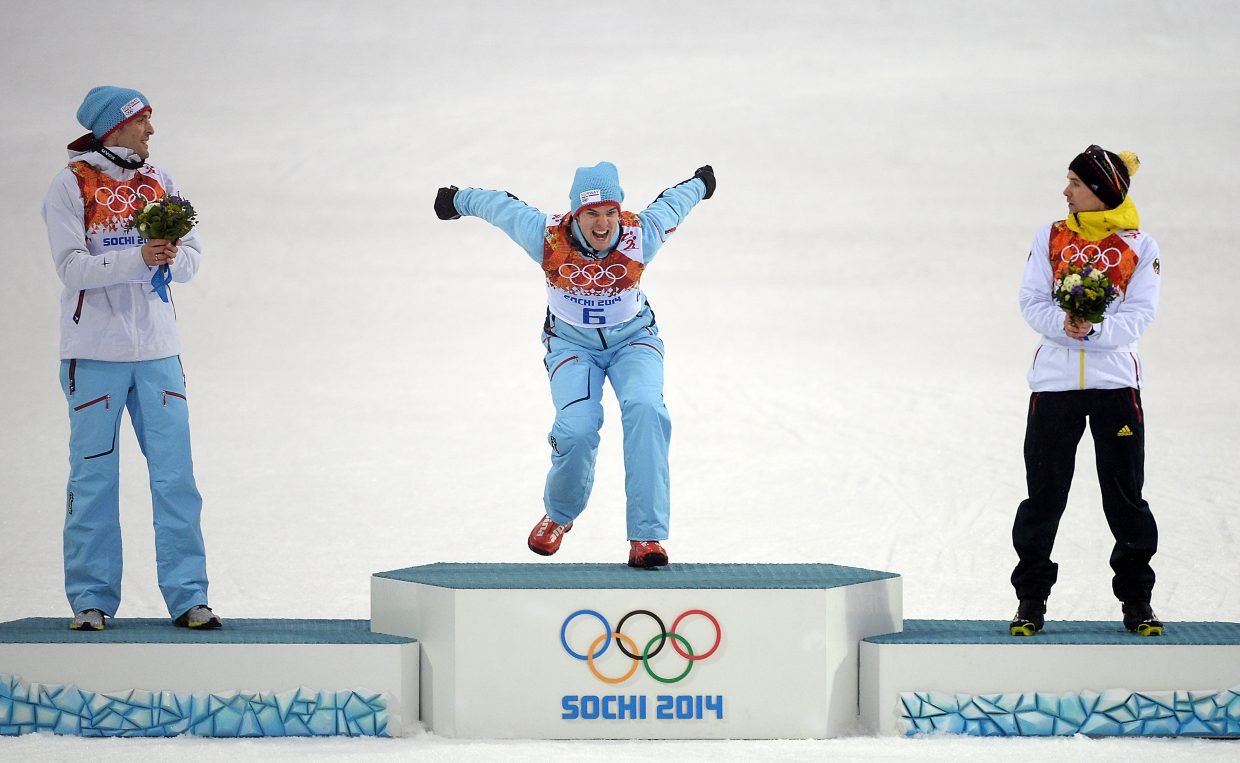 Joergen Graabak, of Norway, leaps onto the podium during the flower ceremony after the large hill Nordic combined competition at the 2014 Winter Olympics. Graabak stuck with a large group of skiers, then won out in the end, winning a gold medal.