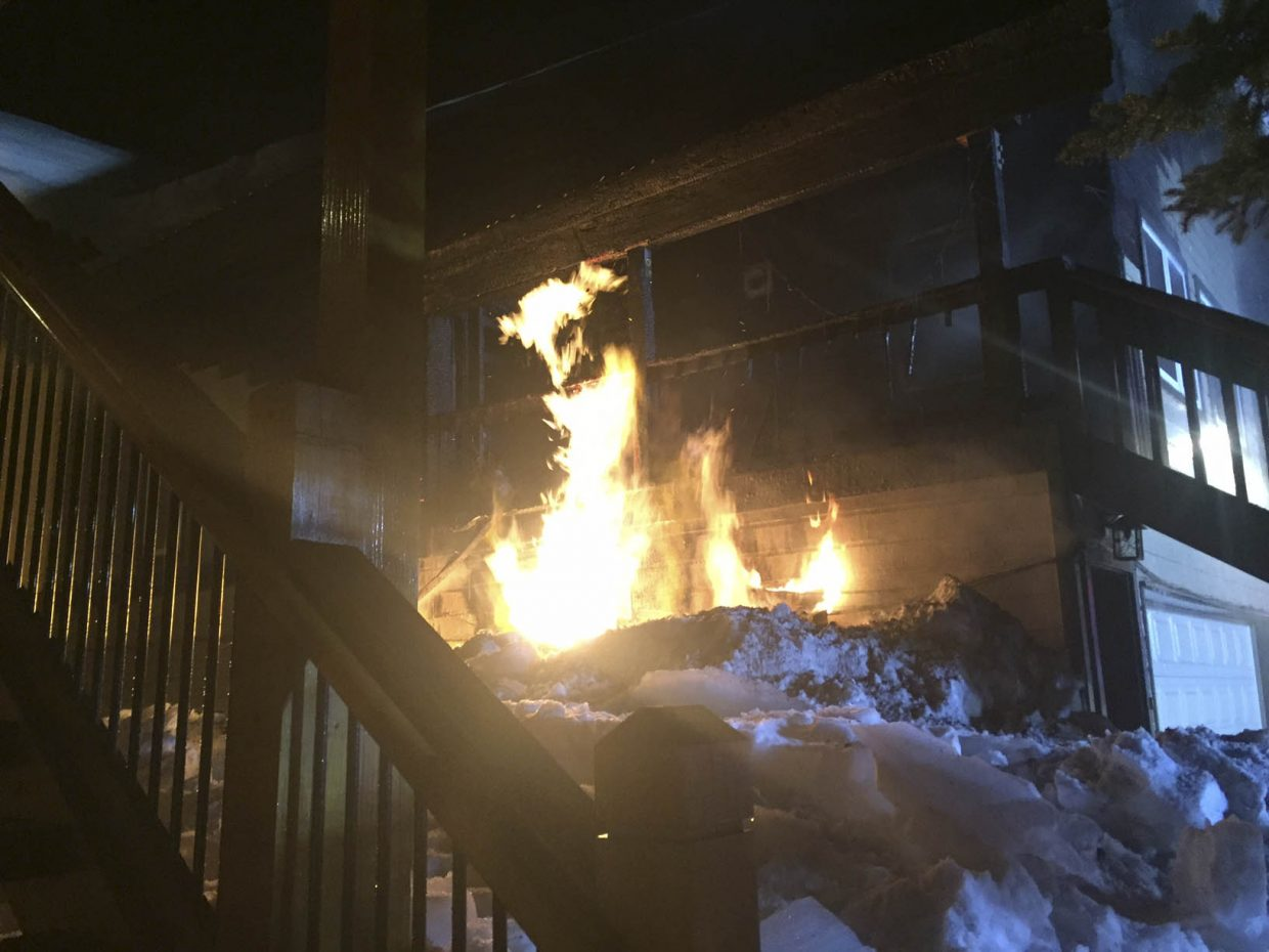 Firefighters cut a hole in the garage wall to reach the turn-off valve for a gas-fueled fire Tuesday night at 466 Cherry Drive.