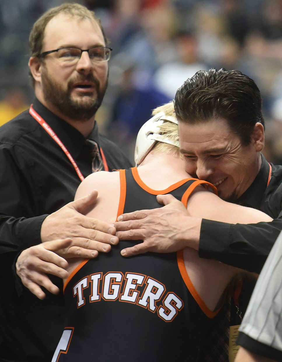 Hayden senior Christan Carson shares a hug with coach Chad Jones on Friday after Carson won his championship semifinal match in overtime at the state wrestling tournament in Denver.