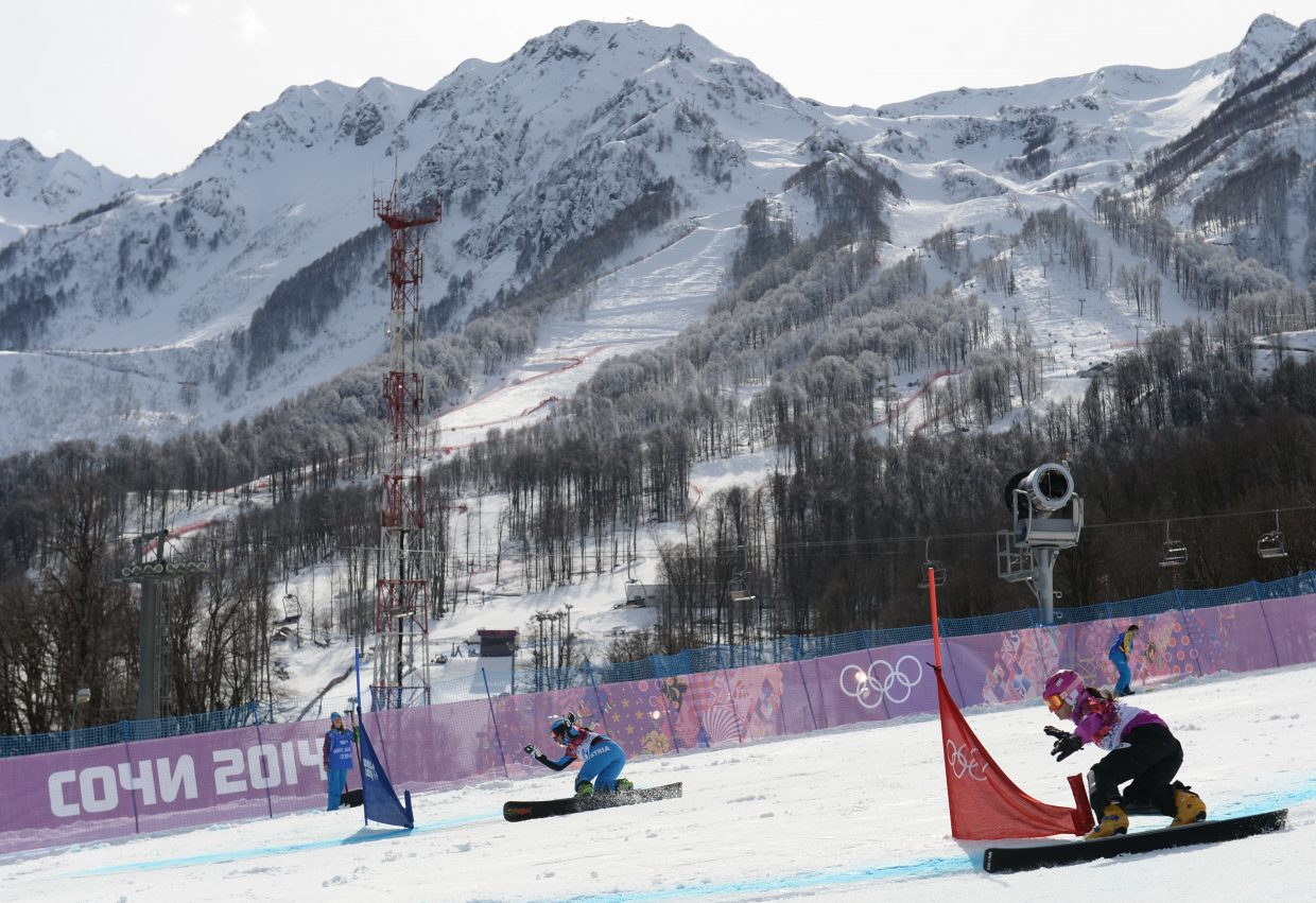 Japan's Tomoka Takeuchi, near, rides Wednesday in the parallel giant slalom event at the 2014 Winter Olympics. This is a shot no one else seemed to want. It's understandable in a way, as there's no obvious and easy way to include the mountains in the background. Ideally, there would have been a spot where the mountains would have been the backdrop with a long lens, a 400mm, for instance. As it was, I used a wide angle zoom, which worked, but included much of the clutter along the side of the run.