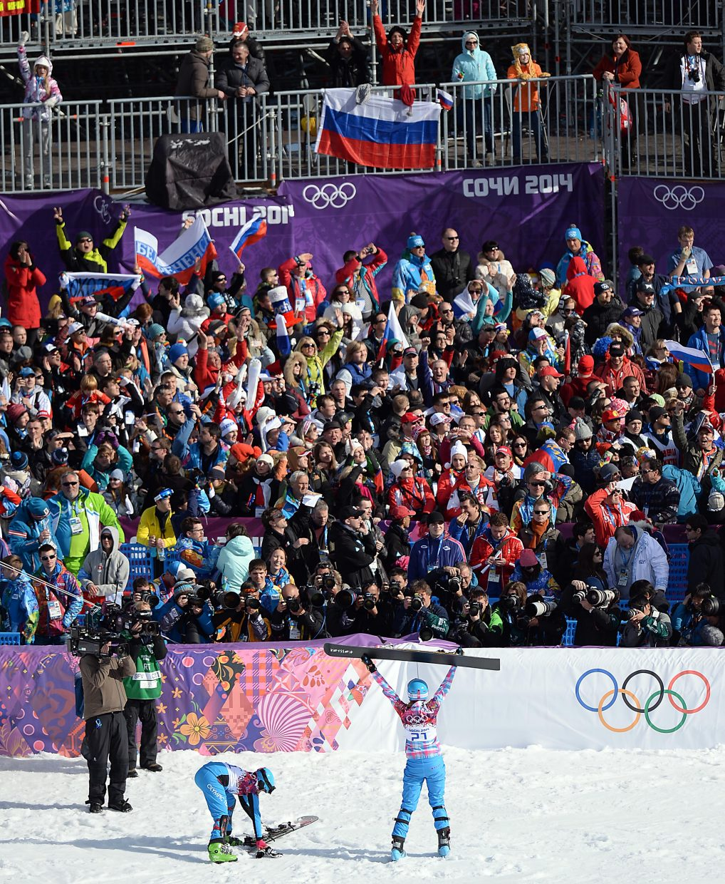 Alena Zavarzina lifts his snowboard above her head after securing a bronze medal on home snow in the women's parallel giant slalom event at the 2014 Winter Olympics.