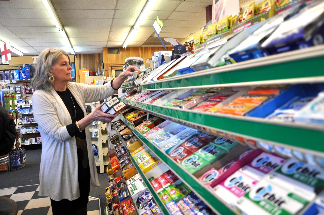 JuDee Duerst restocks mints Tuesday at Lyon's Corner Drug & Soda Fountain in downtown Steamboat Springs. Yampa Valley Data Partners is projecting retail sales growth to continue.