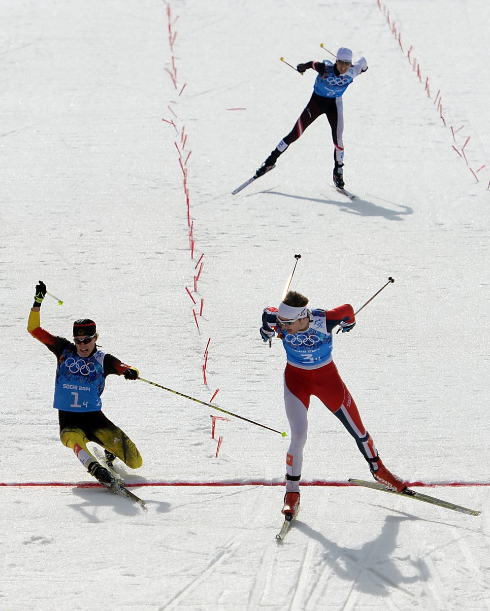 Norway's Joergen Graabak skis across the finish line for a gold medal in the Nordic combined team relay event, ahead of a diving Fabian Riessle of Germany. It was Graabak's second gold medal in Nordic combined at the 2014 Winter Olympics.