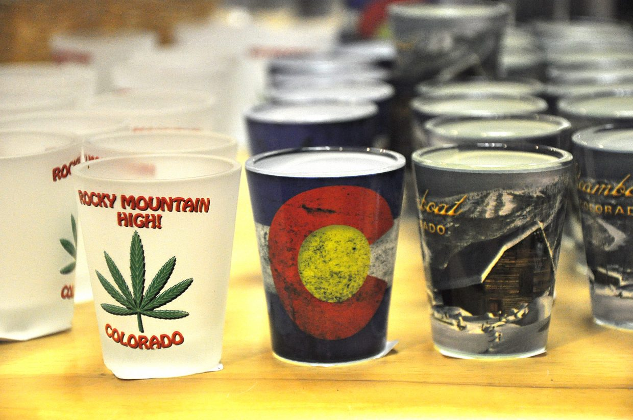A Rocky Mountain High shot glass is for sale at Steamboat Treasures & Tees next to shot glasses featuring the More Barn in Steamboat Springs. Marijuana-themed merchandise is becoming more popular at some local stores following the legalization of the drug.